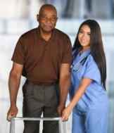 caregiver and senior woman are smiling while walking at the hallway