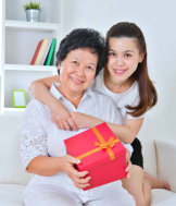 caregiver giving a gift to the senior woman